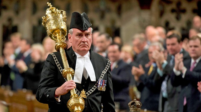 The Sergeant-at-Arms Kevin Vickers receives a standing ovation as he enters the House of Commons Thursday, Oct. 23, 2014 in Ottawa. Vickers was among those who opened fire on Michael Zehaf Bibeau, who stormed Parliament Hill on Wednesday. (AP Photo/The Canadian Press, Adrian Wyld ) ** Usable by LA, DC, CGT and CCT Only **