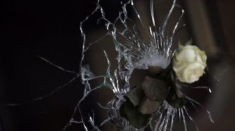 A rose in a bullet hole in the window of a restaurant in the city. Getty Images